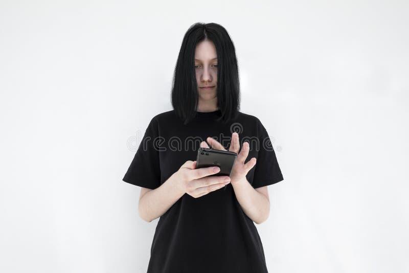 Das Mädchen in einem schwarzen Kleid und mit dem schwarzen Haar mit einem Smartphone in ihren Händen auf einem weißen Hintergrund stockfotografie