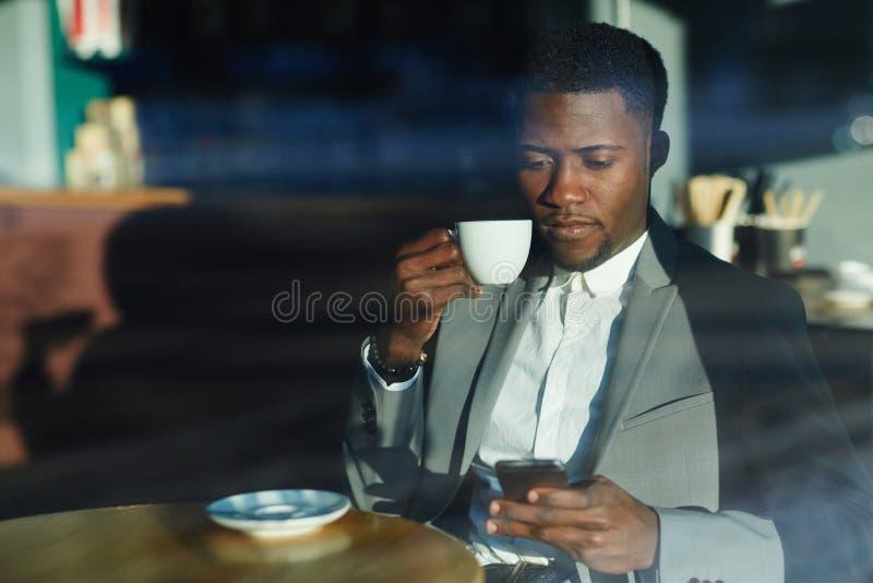Das Mädchen in einem weißen Hausmantel mit einem Tasse Kaffee lizenzfreie stockfotos