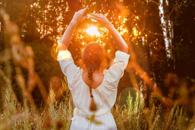 Das Mädchen in einem weißen Kleid betrachtet den Sonnenuntergang im Wald und entspannt sich Frau mit Bortenfrisurmeditation stockfotografie