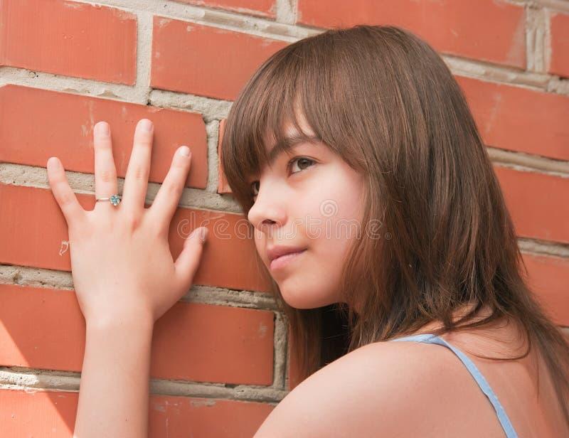 Das Mädchen an einer Backsteinmauer stockfotos
