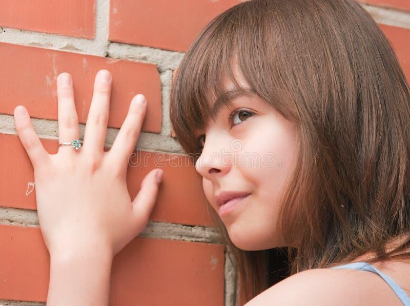 Das Mädchen an einer Backsteinmauer lizenzfreies stockbild