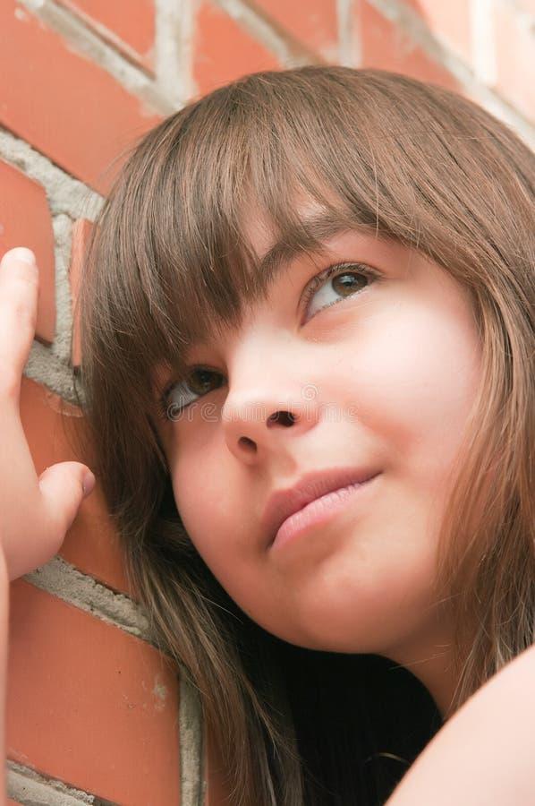 Das Mädchen an einer Backsteinmauer lizenzfreies stockfoto