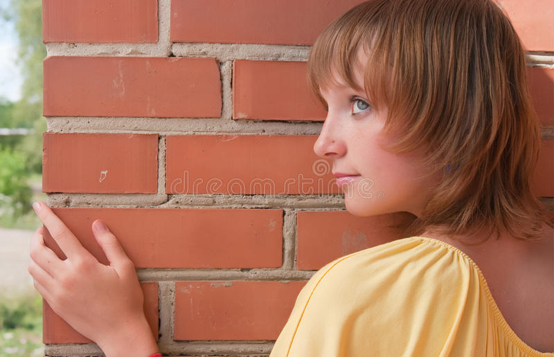 Das Mädchen an einer Backsteinmauer lizenzfreie stockbilder