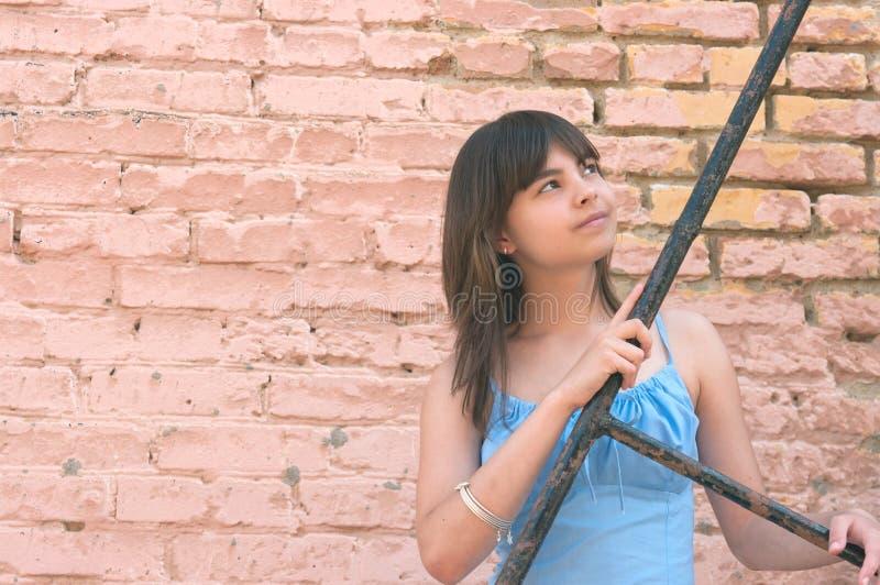 Das Mädchen an einer Backsteinmauer stockfotografie