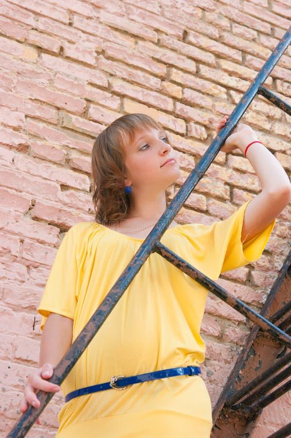 Das Mädchen an einer Backsteinmauer stockbilder