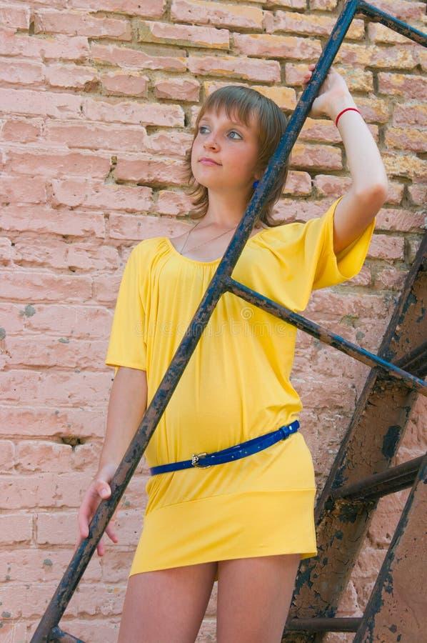 Das Mädchen an einer Backsteinmauer lizenzfreie stockfotos