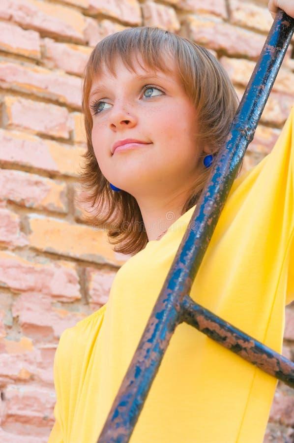 Das Mädchen an einer Backsteinmauer stockbild