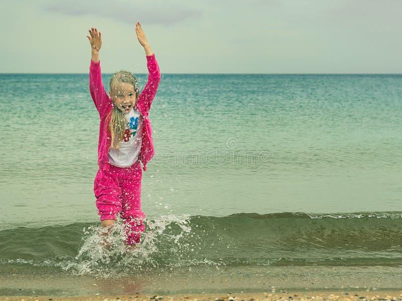 Das Mädchen in einer warmen Klage spielt im kalten Meer lizenzfreies stockbild