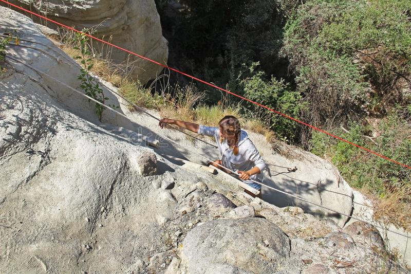 Das Mädchen erhöht sich um den steilen Hang mittels des Seils Felsformation am Ende des Zemi-Tales zwischen Gereme und Uchisar, C lizenzfreie stockbilder