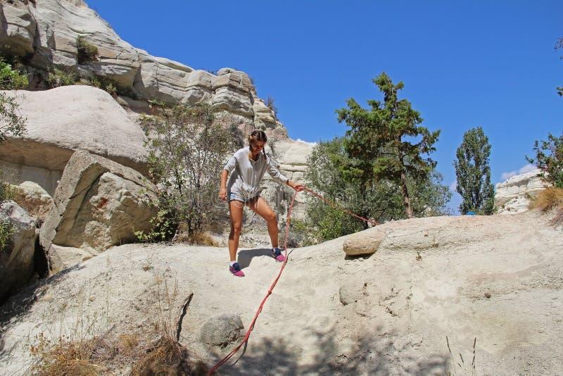 Das Mädchen erhöht sich um den steilen Hang mittels des Seils Felsformation am Ende des Zemi-Tales zwischen Gereme und Uchisar, C lizenzfreie stockfotografie