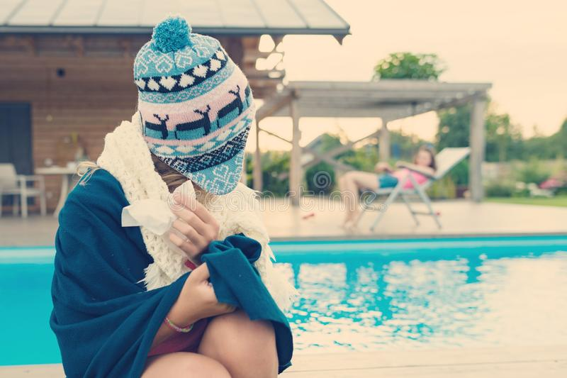 Das Mädchen fing ein kaltes und trug eine warme Strickmütze, Kleidung mit einem Taschentuch, Blicke auf ihren Freund, der vorbei  stockfotos