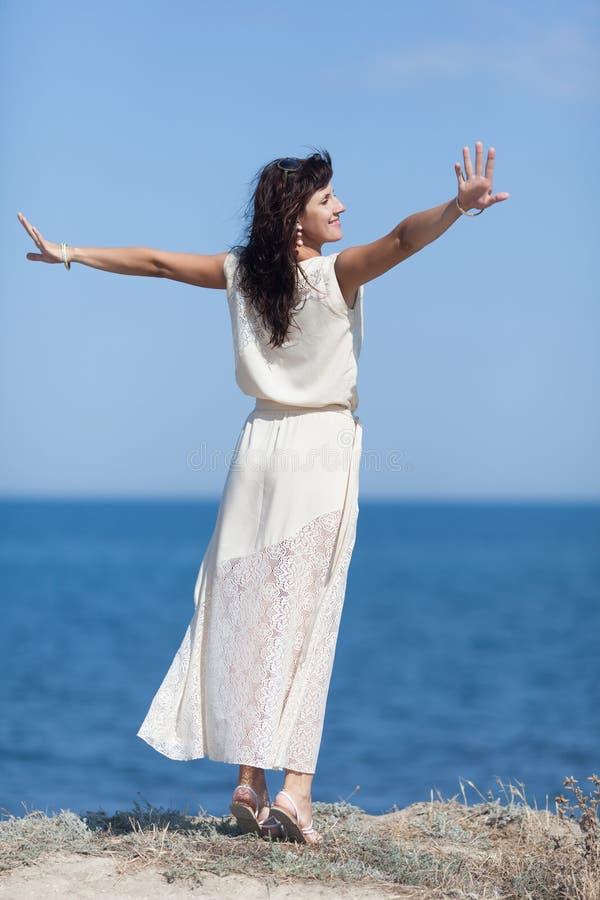 Das Mädchen, das gegen Meer mit den Armen aufwirft, streckte, hintere Ansicht aus lizenzfreie stockbilder