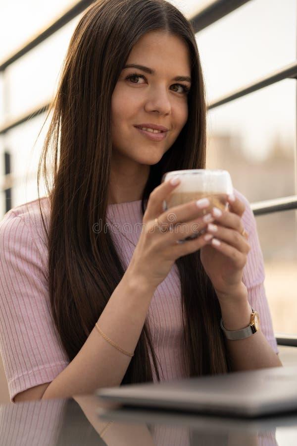 Das Mädchen genießt Kaffee Ein Tasse Kaffee in den weiblichen Händen Ist auf dem Tisch ein geschlossener Laptop lizenzfreie stockbilder