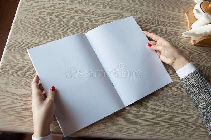 Das Mädchen hält in der Hand das Zeitschriftenmodell das Format A4 stockfotos