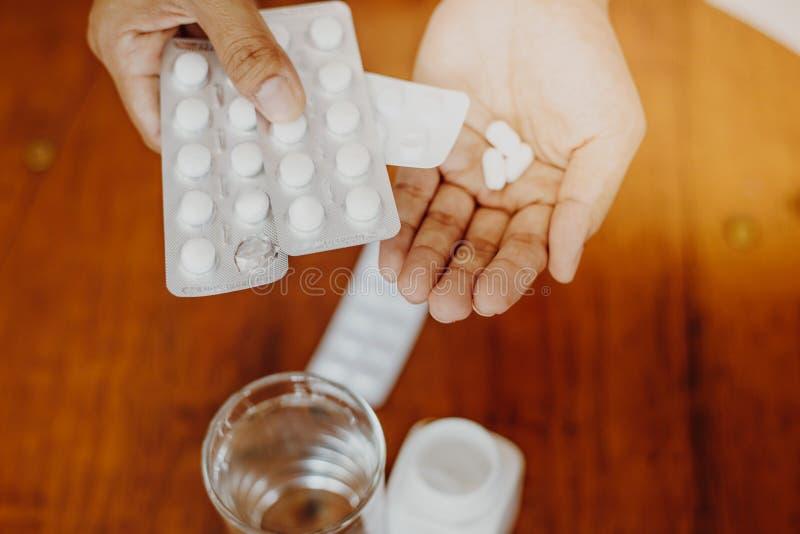 Das Mädchen hält die Medizin in ihrer Hand mit einem Glas Wasser auf einem Holztisch, einnehmen eine Medizin stockfoto