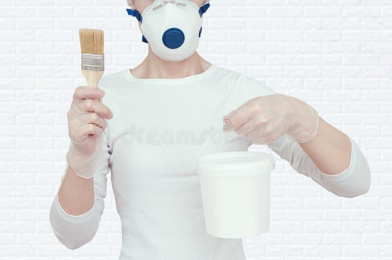 Das Mädchen hält einen Eimer Farbe und eine Bürste für das Malen lizenzfreie stockfotografie