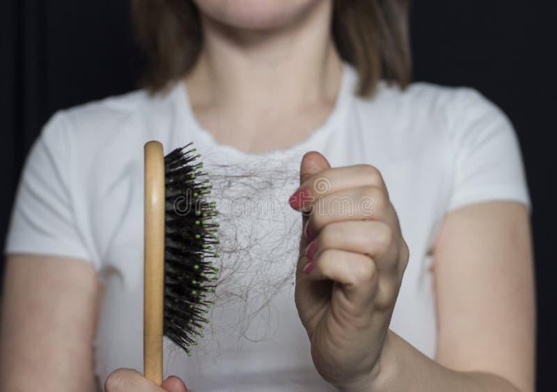 Das Mädchen hält einen Kamm mit ihrem Haar vor ihr Probleme mit dem Haar Haarausfall lizenzfreies stockfoto