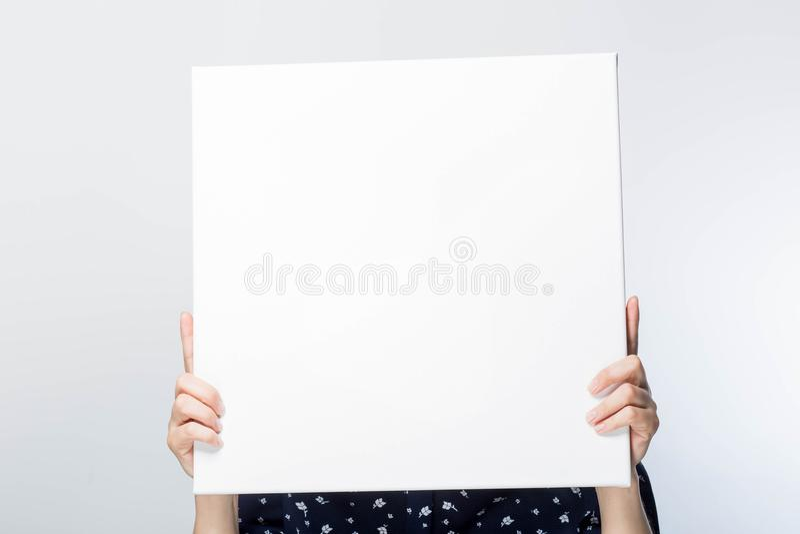 Das Mädchen hält an Hand ein großes Quadrat des Weißbuches in der Mitte, das bedeckte Gesicht, Nahaufnahme, weißer Hintergrund, B lizenzfreie stockfotografie