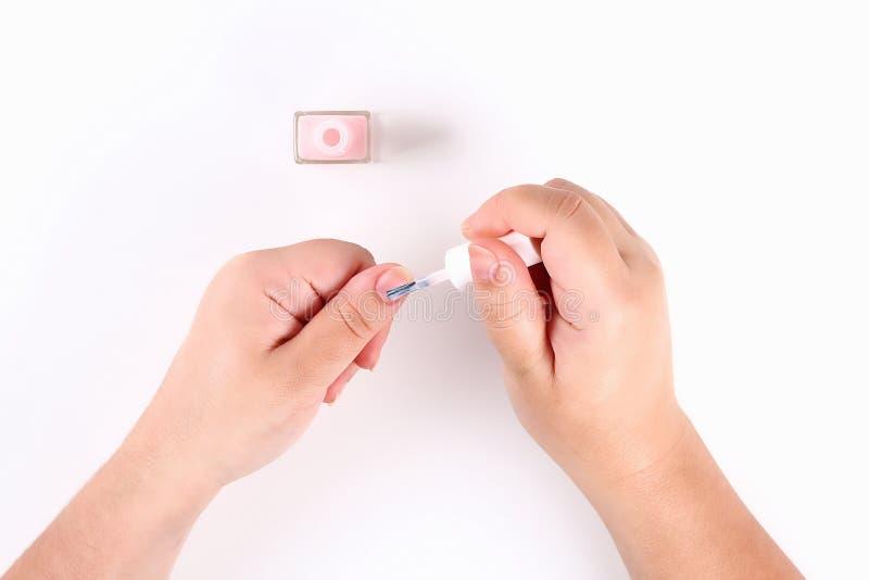 Das Mädchen hält in ihrer Hand einen rosa Nagellack auf weißem Hintergrund Beschneidungspfad eingeschlossen stockfoto