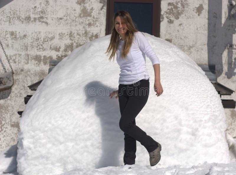 Das Mädchen hat Spaß mit einem Stapel des Schnees lizenzfreie stockbilder