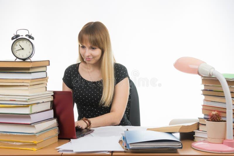 Das Mädchen hinter dem Schreibtisch verunreinigte mit Büchern lächelnd in einer Laptopinformationsversammlung stockfoto