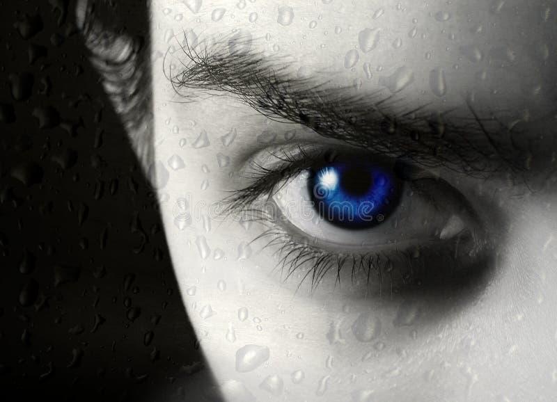 Das Mädchen hinter nassem Glas von einem Regen stockfoto
