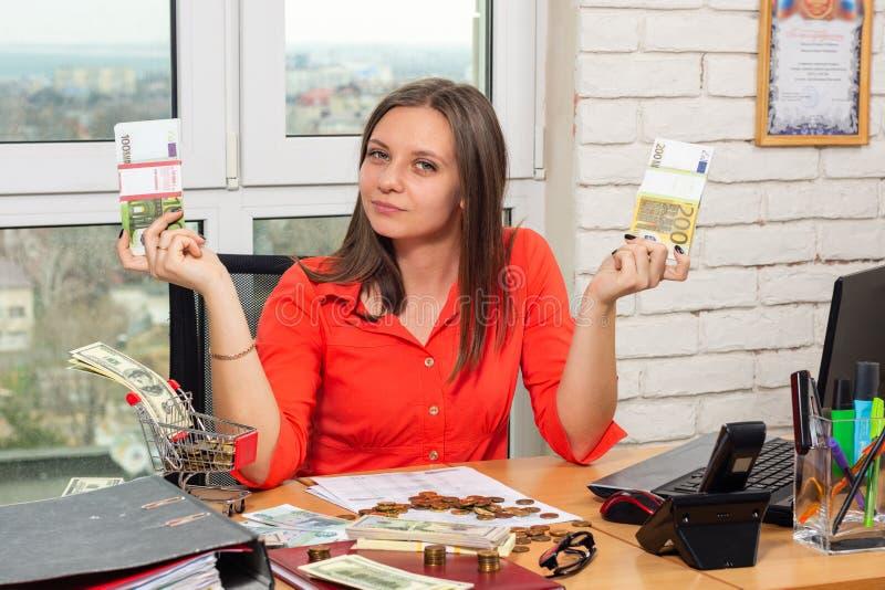 Das Mädchen im Büro zeigt Bündel Geld stockfoto