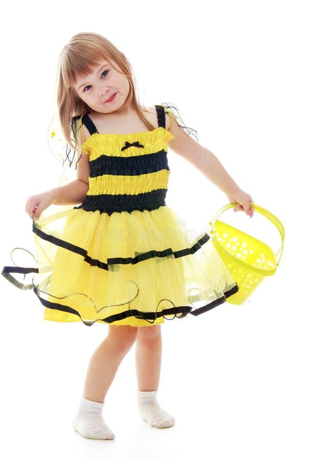 Das Mädchen im Bienenkostüm, das einen Eimer hält lizenzfreie stockfotos