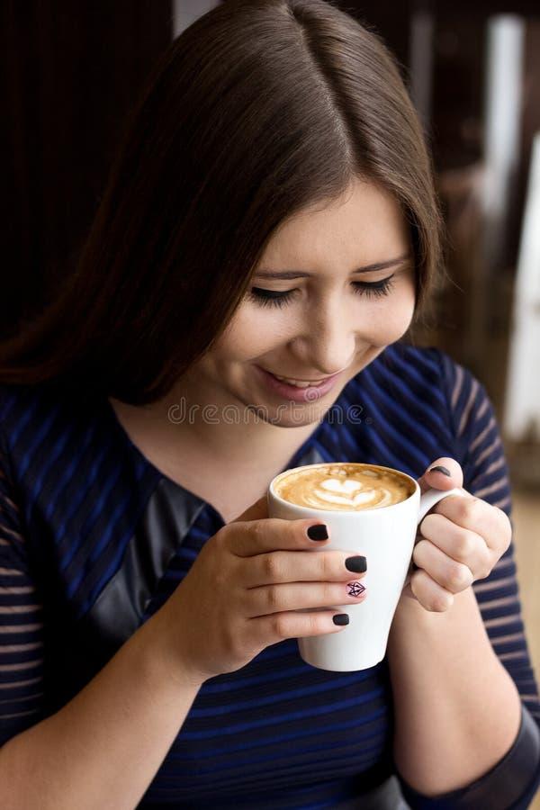 Das Mädchen im blauen Kleid, das mit einer Schale lächelnden Gesichtern des Cappuccinokaffees sitzt stockbilder