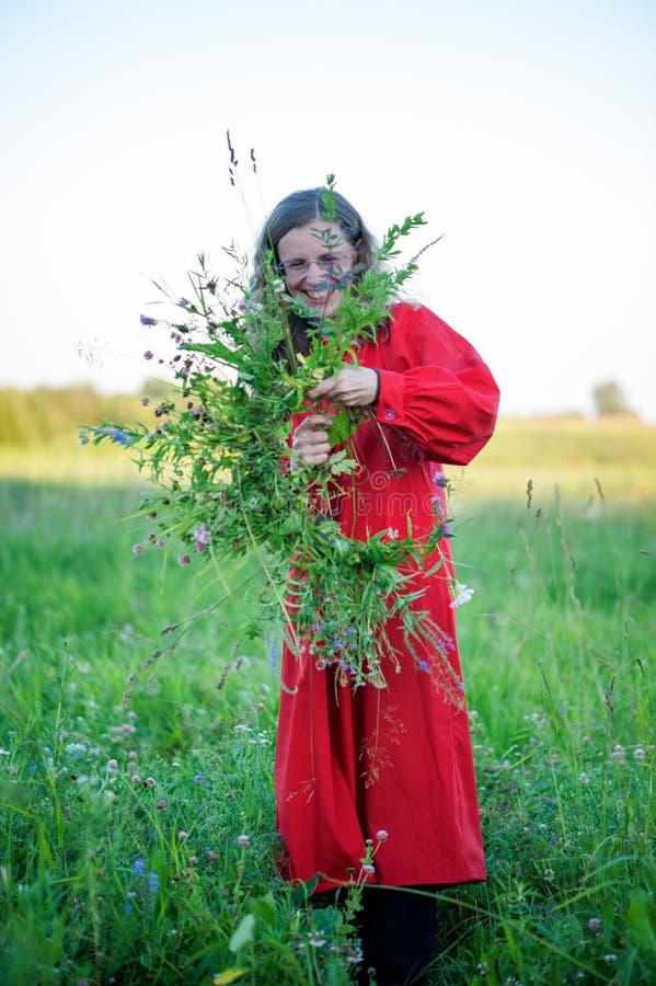 Das Mädchen im roten Kleid macht einen Kranz vom Gras und von den wilden Blumen auf dem Hintergrund einer grünen Wiese lizenzfreie stockfotos