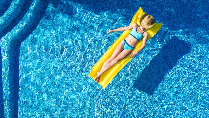 Das Mädchen, das im Swimmingpool sich entspannt, Kind schwimmt auf aufblasbarer Matratze und hat Spaß im Wasser auf Familienurlau lizenzfreie stockbilder