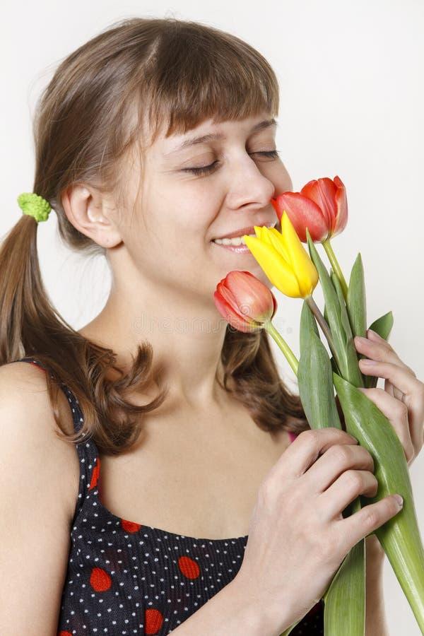 Das Mädchen inhaliert Aroma der Tulpen stockfotografie