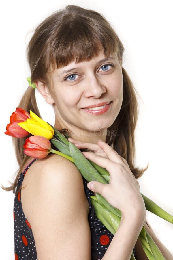Das Mädchen inhaliert Aroma der Tulpen stockfoto