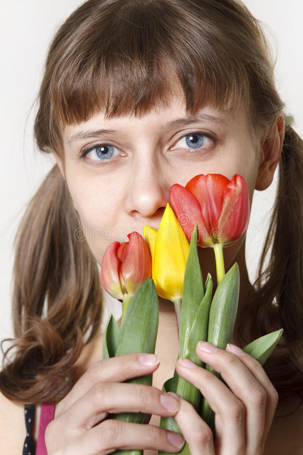 Das Mädchen inhaliert Aroma der Tulpen lizenzfreie stockfotos