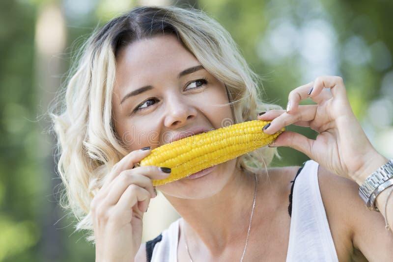 Das Mädchen isst gekochten Zuckermais stockfotografie