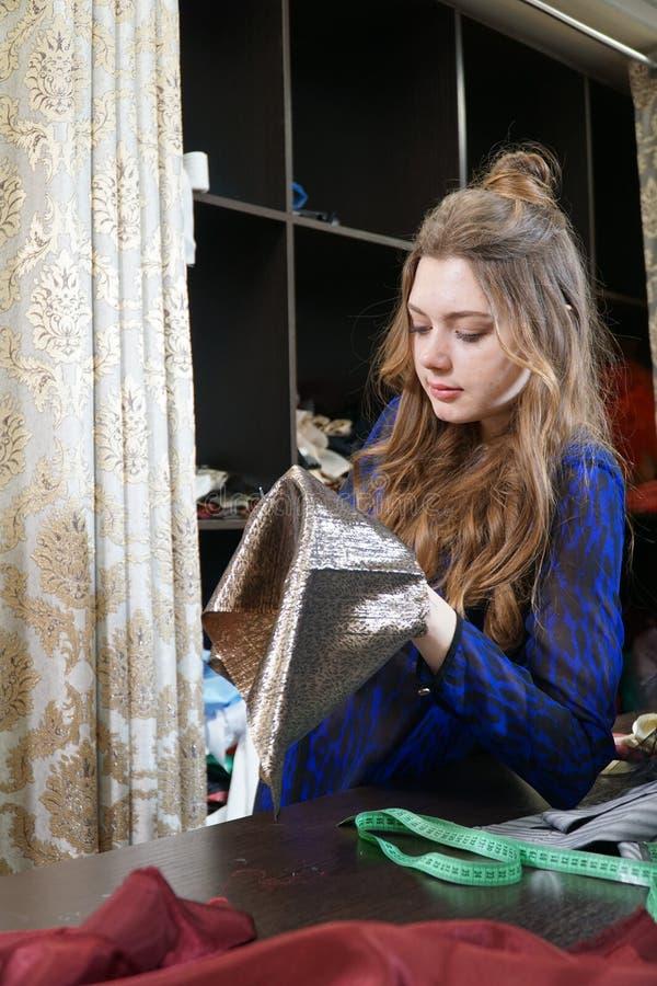 Das Mädchen ist eine Näherin, die in einer nähenden Werkstatt arbeitet lizenzfreies stockbild
