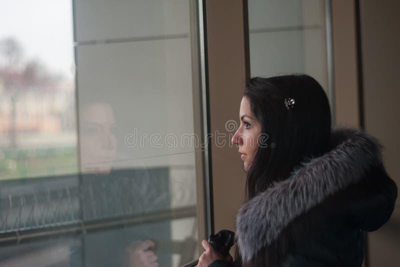 Das Mädchen ist traurig, das Fenster heraus schauend Kunstportr?t eines sch?nen der Junge M?dchens traurig, das durch das Fenster lizenzfreie stockbilder