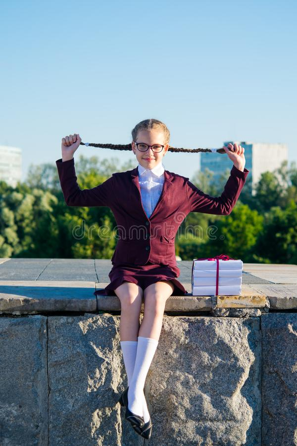 Das Mädchen ist, ziehend sitzend und für Zöpfe beim Spielen Im Freien lächeln stockfotos