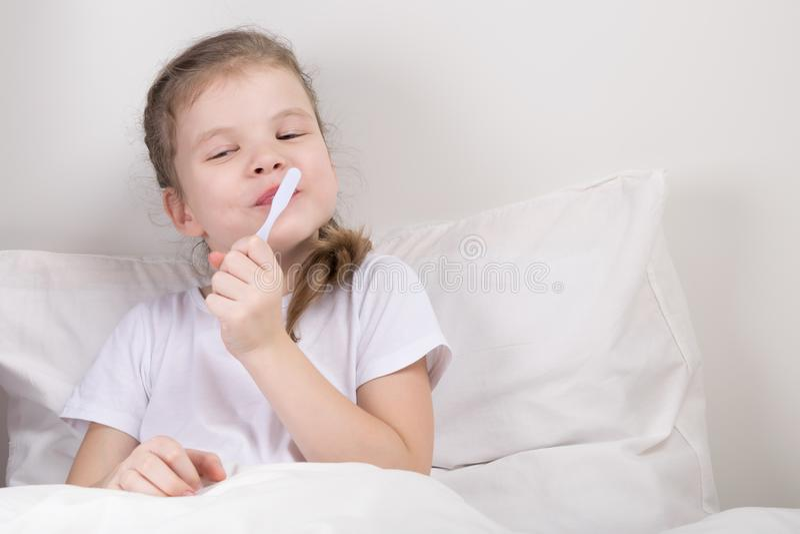 Das Mädchen kümmert sich um ihren Zähnen und gibt sich das Verlassen kein Bett hin stockfotos