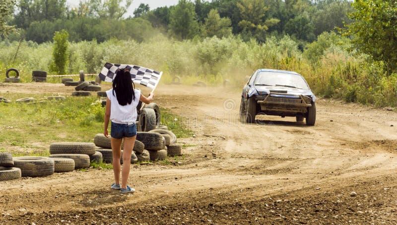 Das Mädchen kündigt eine Zielflagge am Ende der Fahrt an stockfoto
