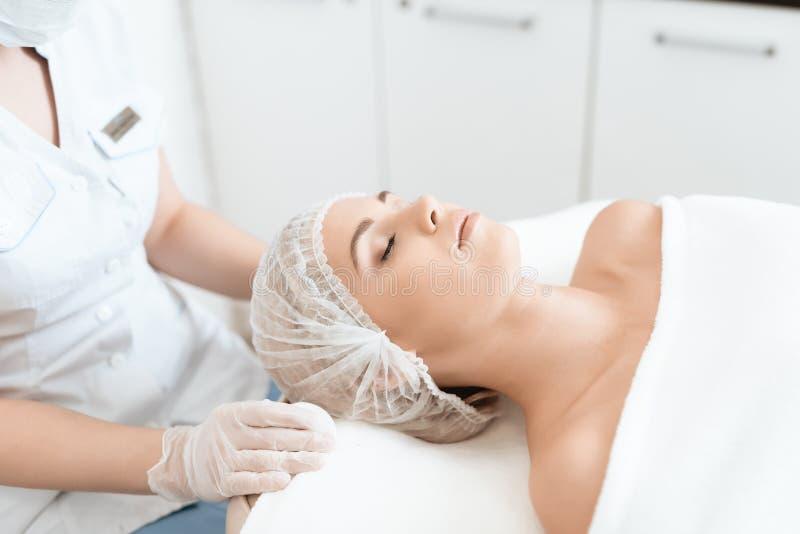Das Mädchen kam zum Badekurortsalon für Laser-Haarabbau Die Frau liegt auf der Couch, der Doktor vorbereitet sie für Verfahren stockbild