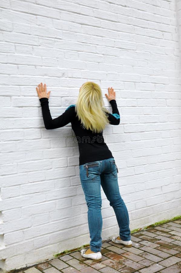 Das Mädchen kostet nahe einer weißen Wand lizenzfreies stockfoto