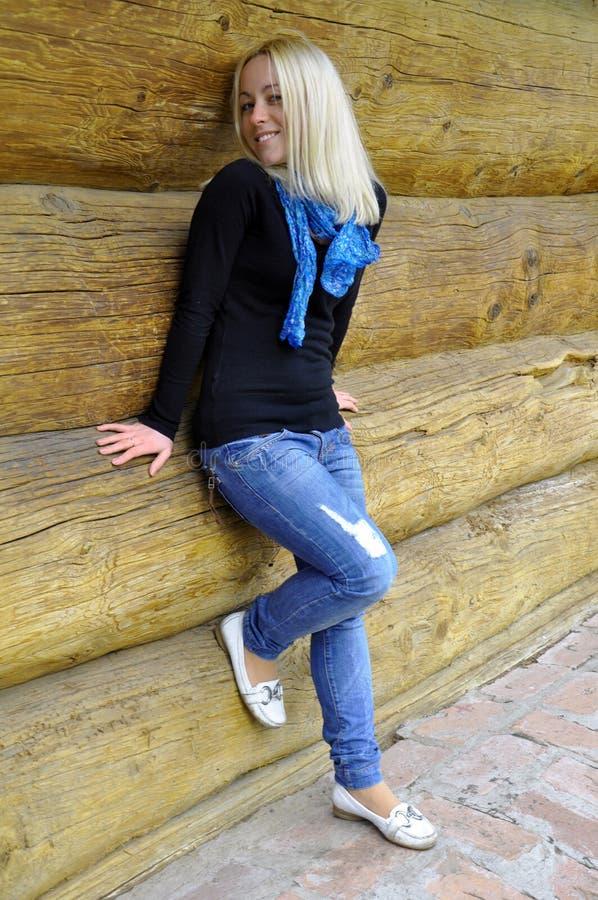 Das Mädchen lächelt nahe einer Protokollhütte lizenzfreies stockbild