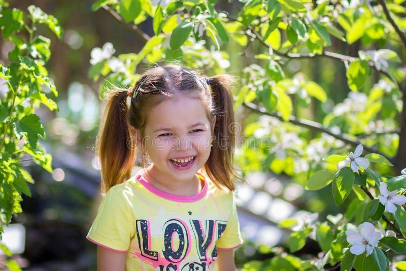 Das Mädchen lacht Stellung nahe dem blühenden Baum stockfotos