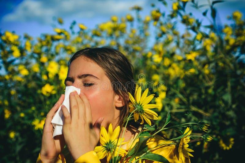 Das Mädchen leidet unter Pollenallergie während des Blühens und benutzt Servietten Blühende Bäume im Hintergrund Hübsche Frau erh stockbilder