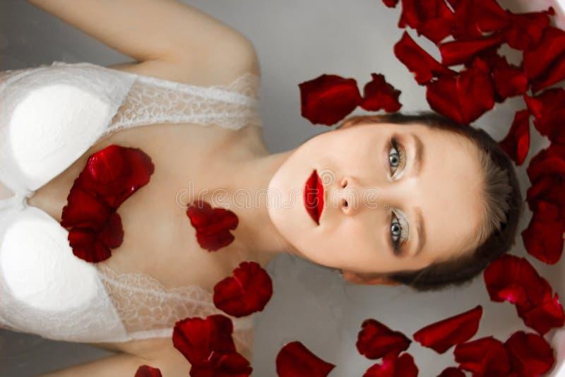 Das Mädchen liegt im Badezimmer mit den rosafarbenen Blumenblättern Ein Wellnessbad mit Rosen stockfoto