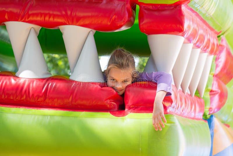 Das Mädchen liegt im Mund des Drachen auf einer weichen aufblasbaren Trampoline stockbild