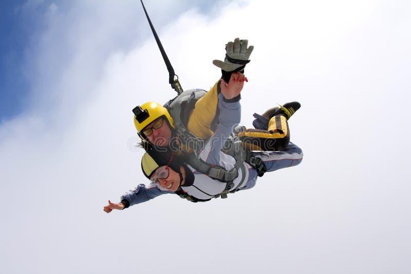 Das Mädchen mit dem Ausbilder im freien Fall Im freien Fall springen im blauen Himmel lizenzfreie stockbilder