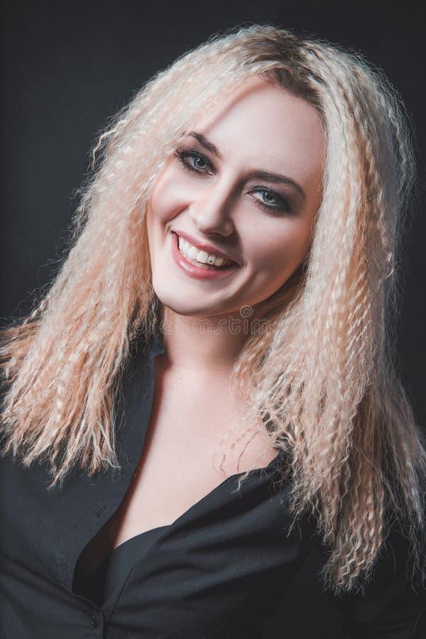 Das Mädchen mit dem blonden Haar auf schwarzem Hintergrund stockfoto