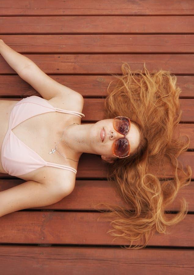 Das Mädchen mit dem roten Haar liegt auf den braunen Brettern lizenzfreie stockfotografie
